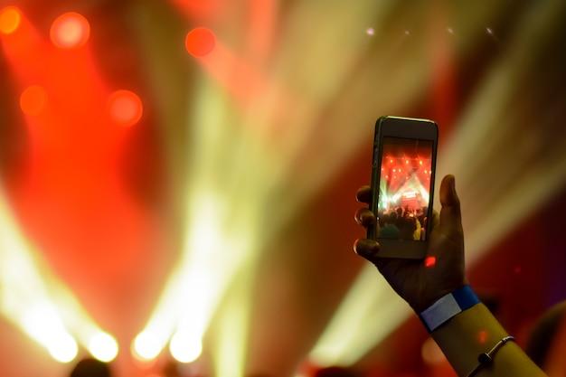 赤いライトの光の中で歌うアーティストの背景にスマートフォンを持つ手のシルエット