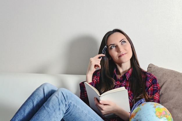 幸せな若いブルネットの女性は日記と白いソファの上に横たわる旅の休暇を夢見て、