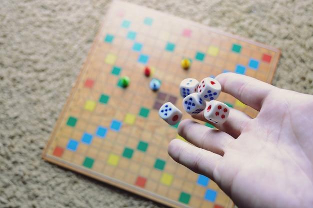 白いサイコロ背景カラフルなぼやけたボードゲームを投げている手