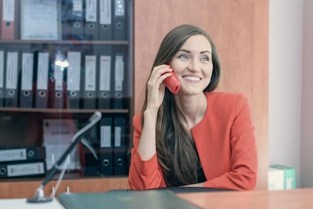 赤いスーツの若い女の子は、友達と電話で話している仕事に戻って座っています。