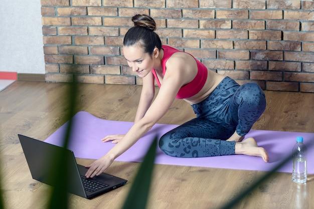 スポーツウェアの女の子は床に座っていると水のボトルとラップトップでソーシャルネットワークを見ながら演習から休憩を取る