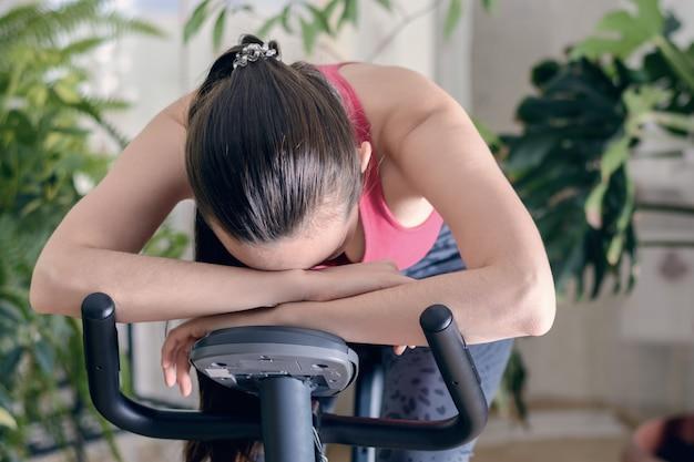 疲れやめまいがするようなワークアウト中のエクササイズバイクでの自宅での若い健康的なフィット女性トレーニング、彼の手に彼の頭を下げた。