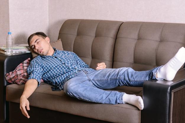 Спящий молодой человек на диване в комнате, усталый после работы, пьяный после вечеринки.