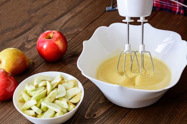 Замесить тесто или тесто для яблочно-грушевого пирога или кекса или блина. закрыть в деревянный стол с ингредиентами
