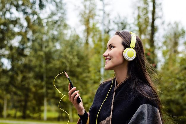 静かな公園でヘッドフォンでスマートフォンから音楽を聴く若い幸せな女