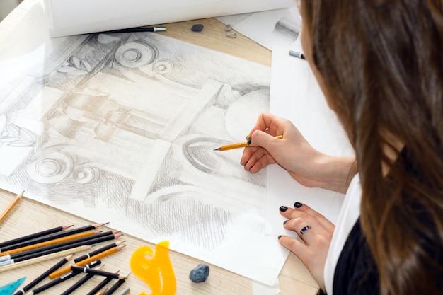 光と影のパターンを準備する鉛筆で学生建築家の手、木製のテーブルのデザイン手すり子クローズアップ
