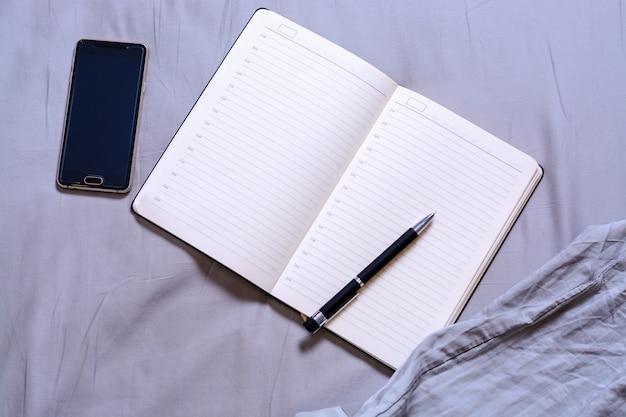 Открыть блокнот с черной ручкой с надписью и место для текста лежит на кровати с помощью смартфона. концепция фриланса в день, планирование дня, постановка целей.