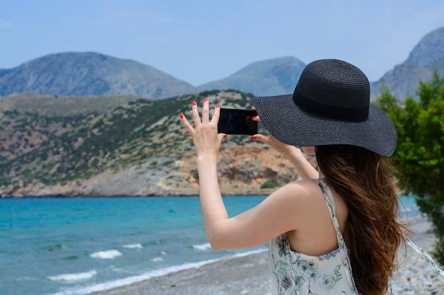 Женщина путешественник делает себе на заднем плане красивый естественный вид горы на острове. концепция - туризм, путешествия фото из отпуска.