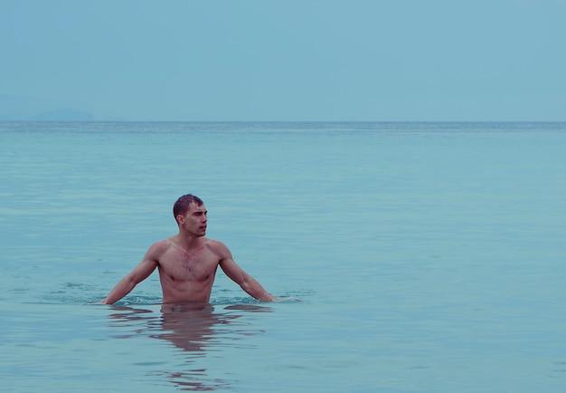 裸の筋肉胴を示す海または海の魅力的な若い運動男
