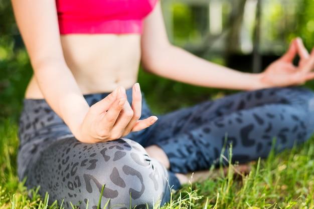 太陽の下で緑の芝生で瞑想の女性のクローズアップ