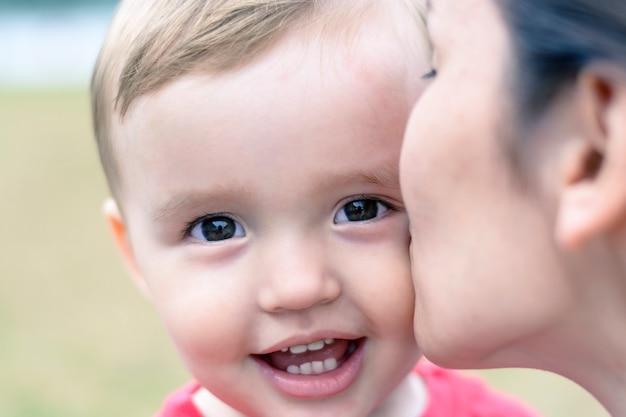 母は小さな男の子の頬にキスします。