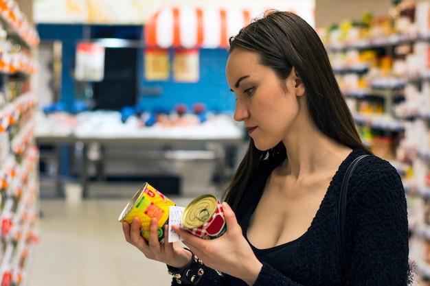 スーパーで買い物美しいブルネットの女性。非遺伝子組み換え食品の選択。