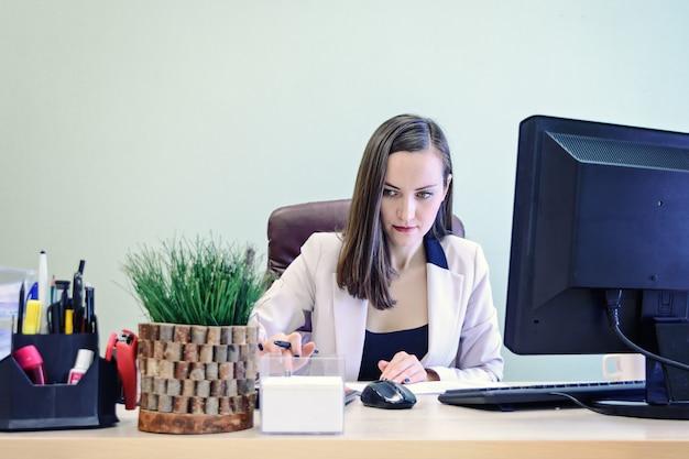 Молодой бизнес женщина работает над столом в кабинете, экономист бухгалтер финансовой отчетности, проверяет правильность документов.