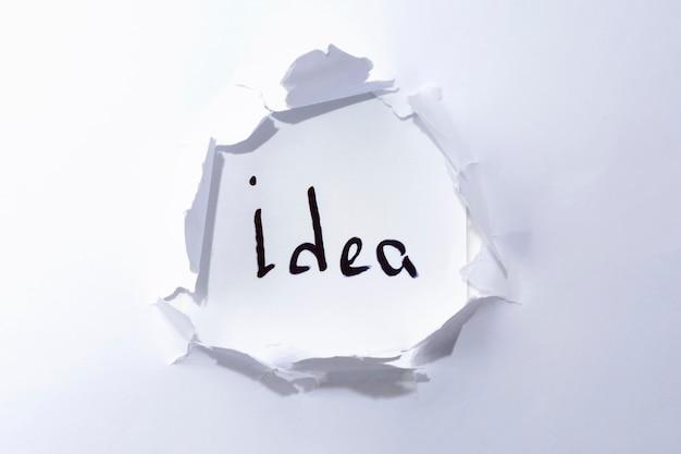 紙の穴に白い背景の上のアイデア