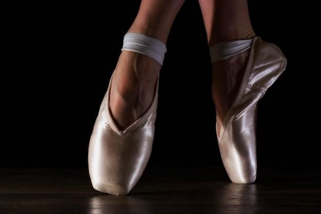 黒い床のポアントでクラシックバレリーナの足をクローズアップ