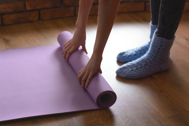 Женщина в синих шерстяных носках превращается в фиолетовый коврик для йоги и фитнеса на паркетном полу в комнате