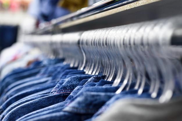 デニムのシャツがハンガーに一列に掛かっています。洋服店。スタイル