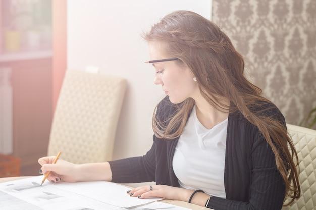 Фронтальный портрет молодой ученицы занимается за столом, рисует эскизы, зарисовки, планы, архитектуру. обучение и практика