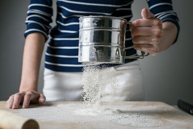 女性の手は、調理用の白い小麦粉を木の板に振りかけます。飛行中の動的凍結粉