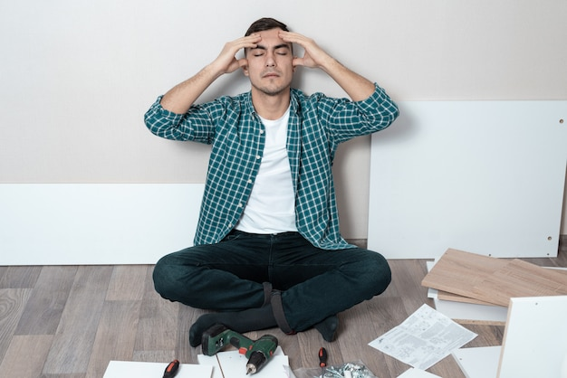 Мужчина на полу держит голову, трудности в сборке мебели.