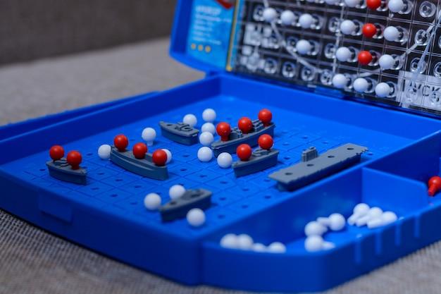 Игра-линкор крупным планом. игрушечные военные корабли и подводные лодки размещаются на игровом поле. стратегия, мышление, победа, поражение