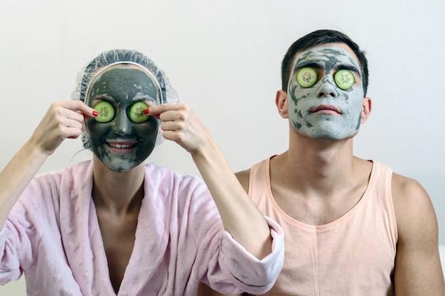 彼の顔に粘土のマスクと彼の前にキュウリを持つ夫婦の正面肖像画。自宅のスパ。スキンケア