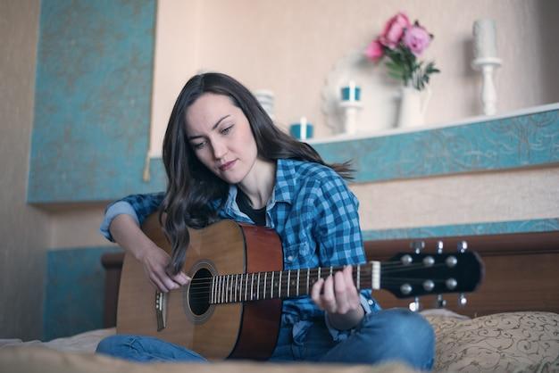 寝室のベッドでアコースティックギターを教えることに従事している女性の自然な肖像画
