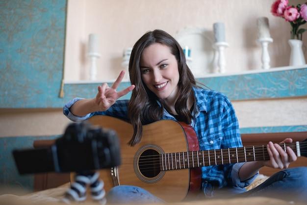 アコースティックギターを持つ女性ブロガーの感情的な肖像画は、カメラの平和のジェスチャーを示しています