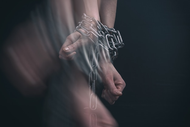 Женские руки прикованы цепью