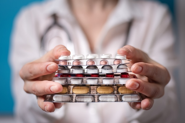 女性医師は錠剤のスタックを保持します