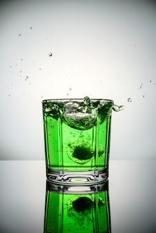 緑のカクテルの氷からはね