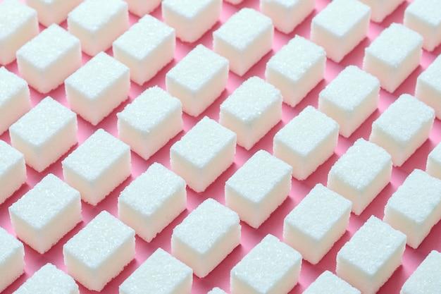 Кубики рафинированного белого сахара правильной геометрической формы на розовом фоне.