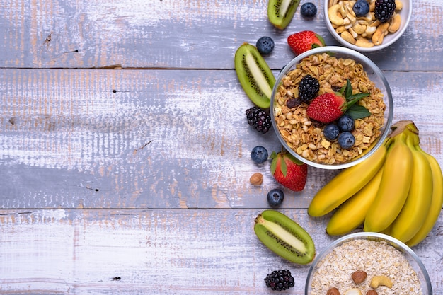 健康的な朝食の食材。ミューズリー、ナッツ、フルーツ、ベリー、素朴な木製の背景にバナナ。