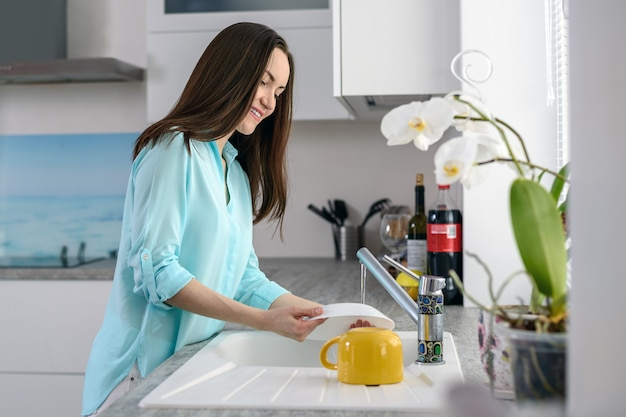 Молодая женщина моет посуду перед окном в мягком свете