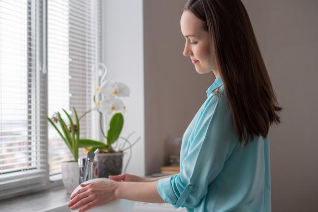主婦は朝の柔らかな光の中で、台所の窓の前で皿を洗う