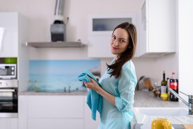 明るいキッチンのインテリアで彼女の手で皿タオルを持つ若いブルネットの側からの肖像画