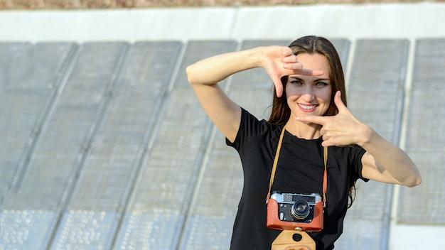 街でレトロなカメラで写真を作る幸せなブルネットの女性