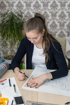 テーブルに集中している若い学生の肖像画は、建築デザインの図面に取り組んでいます