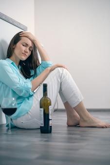Молодая женщина сидит на полу пьет вино, алкоголизм, депрессию, развод