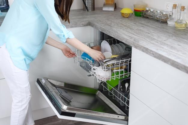 女性は、食器洗い機からきれいな料理を引っ張るクローズアップ