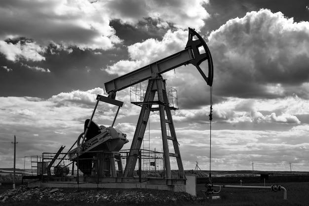 曇り空、暗いレトロな調子の背景に石油リグ