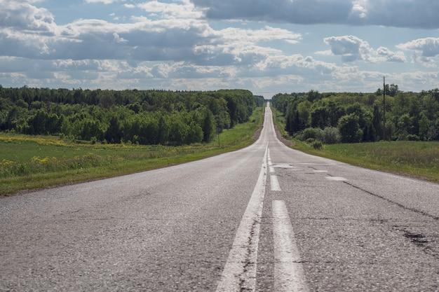 Серая асфальтовая дорога с белыми отметинами, уходящая в горизонт, концепция жизни, достижение целей, сильный характер