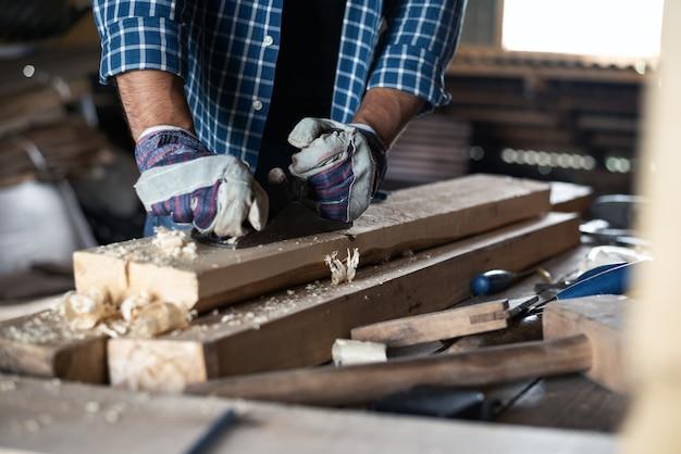 Крупный план мужских рук в перчатках с рубанком обрабатывает деревянную доску, ручной труд, поделки, рабочий процесс