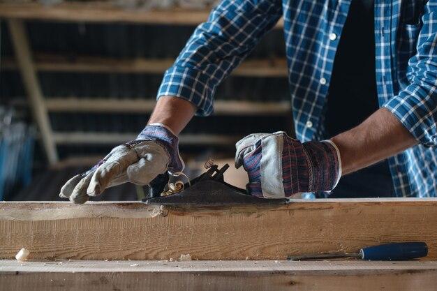Крупным планом руки плотника в перчатках со строгальным станком, ручка из дерева, ручной труд, безопасность, правила работы с инструментом