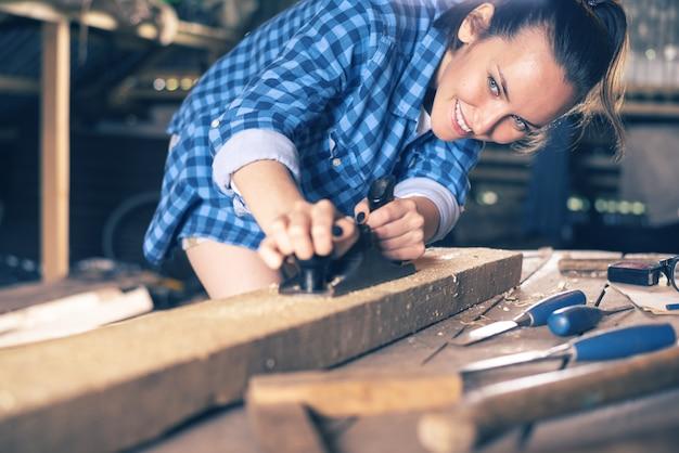 Плотник девушки работая с строгальным станком в домашней мастерской, тонизированный конец-вверх