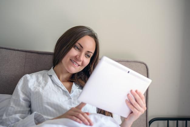 Крупным планом брюнетка женщина использует планшет, лежа в постели рано утром