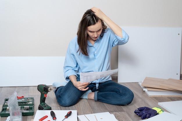 家具を組み立てるための指示を持つ青いシャツを着た思いやりのある女性が床に座っています。