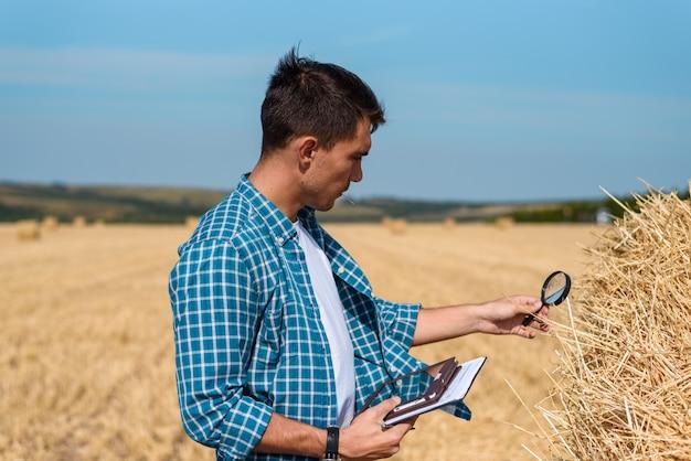 Ботаник-мужчина с увеличительным стеклом и планшетом изучает сенокос