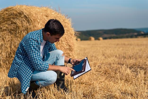 Молодой фермер-агроном-ботаник изучает сенокошение с помощью увеличительного стекла и таблетки в поле против стога сена