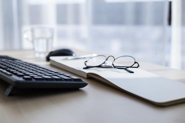 Макрофотография ноутбук, очки, чашка кофе и другие предметы на белом рабочем столе с размытым городом в фоновом режиме